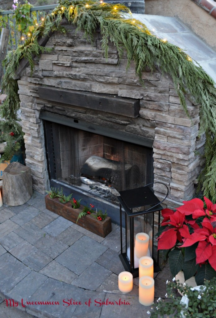 Beautiful Stacked Stone Fireplace decorated with fresh greens for Christmas