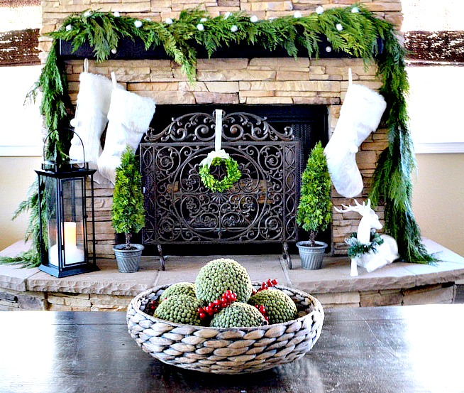 Rustic Fireplace with fresh garland, knitted stockings and reindeer.