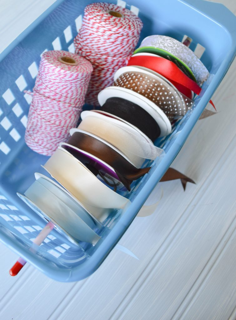 Take a dollar store plastic bin and turn it into a organized ribbon dispenser