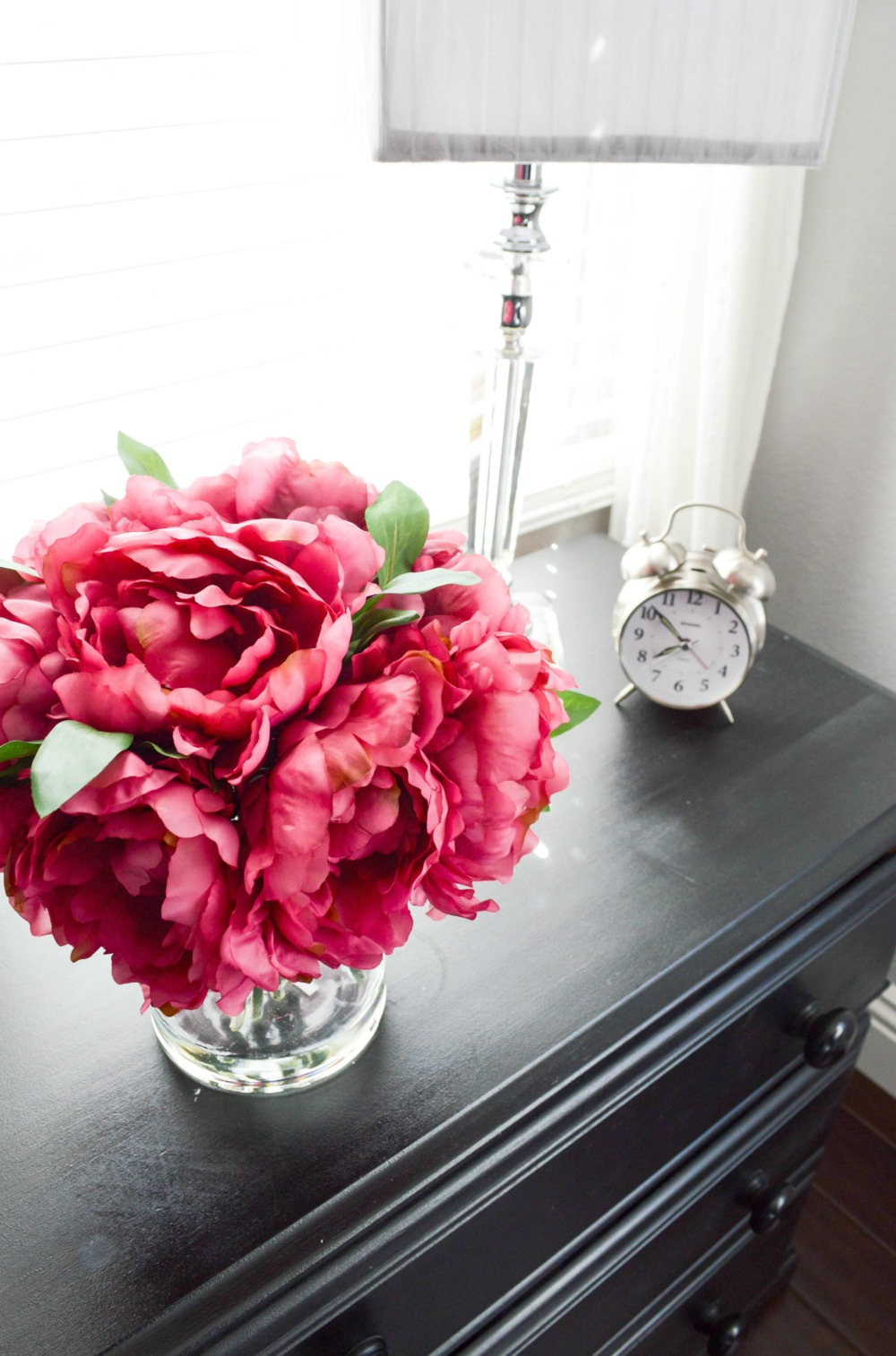 Vibrant pink flowers against a black and gray dresser