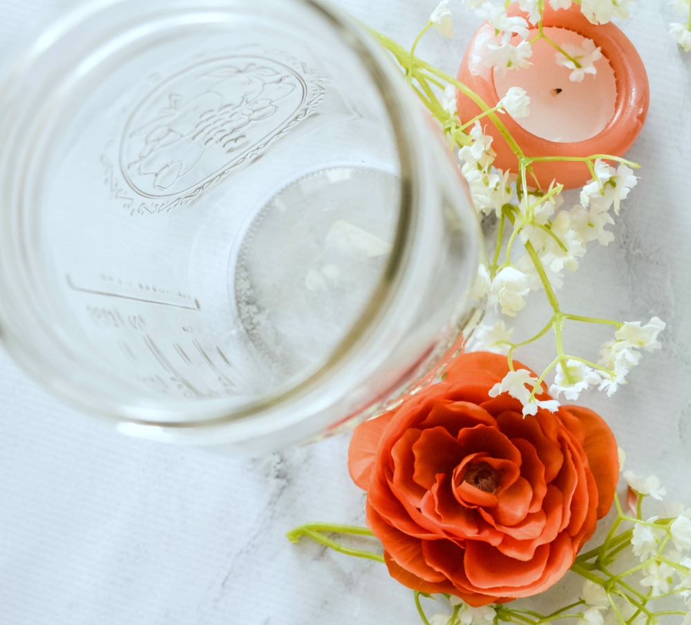 Decorative luminary in a mason jars using faux flowers and a floating candle