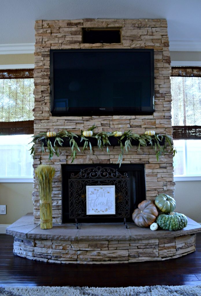 stacked stone brick fireplace decorated for fall