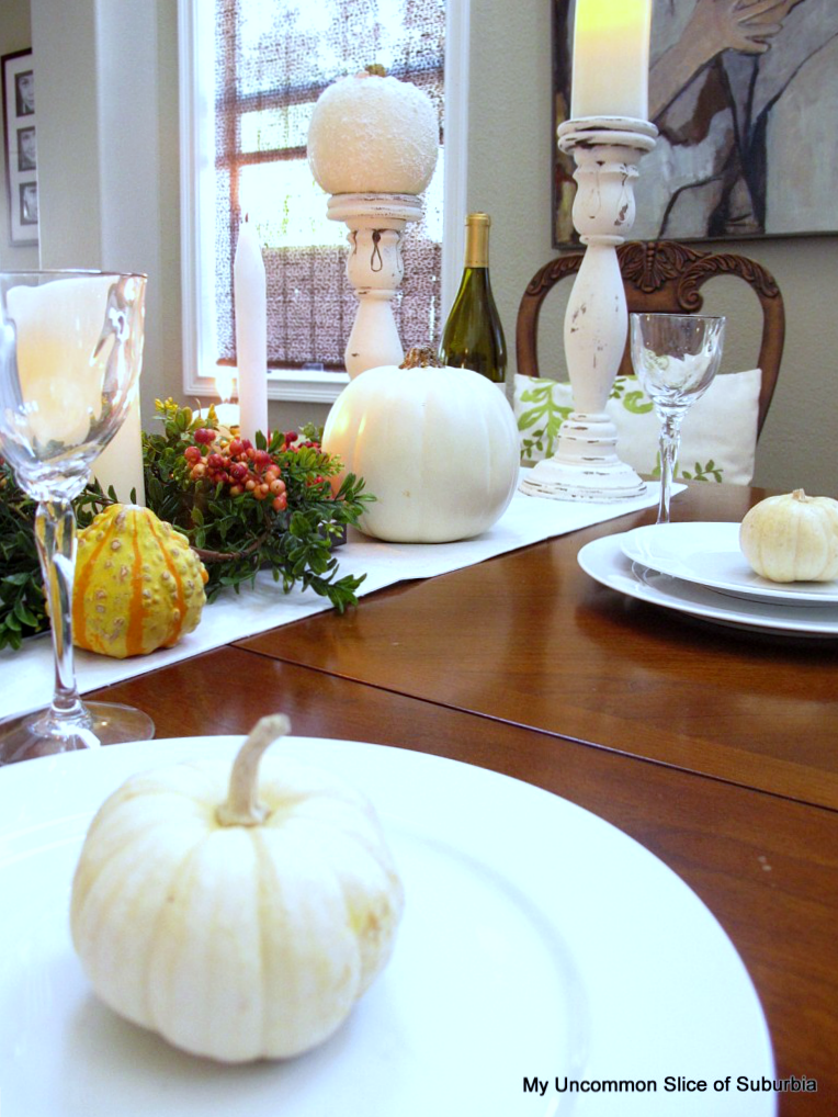 line up mini pumpkins down the center of the table with candles, flowers and gourds for a beautiful thanksgiving display